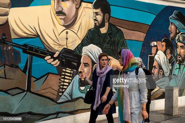 Women walk past a political war mural on a wall in Tehran Iran on Sunday Aug 5 2018 Irans central bank acting on the eve of US sanctions scrapped...