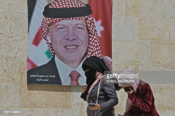 Women walk past a poster of Jordan's King Abdullah II on a street in the capital Amman, on April 6 after a security crackdown revealed tensions in...