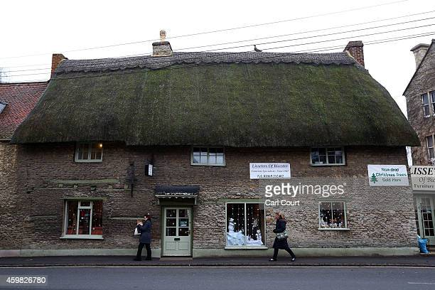 Women walk past a shop in a thatched house on December 2 2014 in Bicester England Up to 13000 new homes are due to be built on the edge of the town...