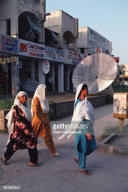 Women walk past a shop selling satellite dishes in the nation's capital city, Islamabad..