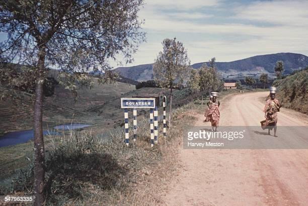 Women walk past a sign showing the Equator line in Uganda circa 1960