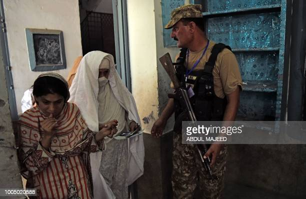 Women walk past a soldier as they arrive to cast their vote during Pakistan's general election at a polling station during the general election in...