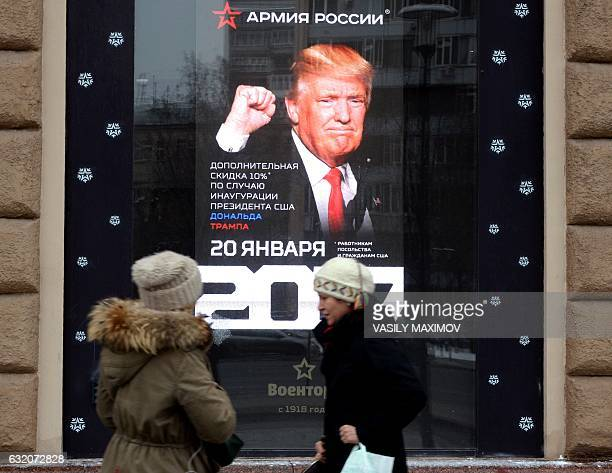 Women walk past an advertising board of a Voentorg shop displaying a portrait of US Presidentelect Donald Trump in central Moscow on January 19 2017...