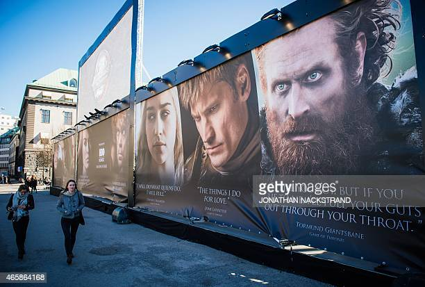 Women walk past an advertising poster to promote the HBO American fantasy drama television series Game of Thrones outside the International Game of...