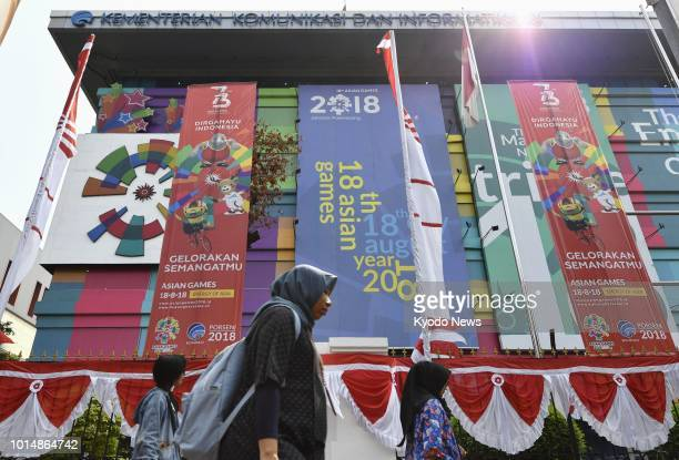 Women walk past banners for the Asian Games 2018 in Jakarta on Aug 8 2018 The event will be held from Aug 18 through Sep 2 in Palembang and the...