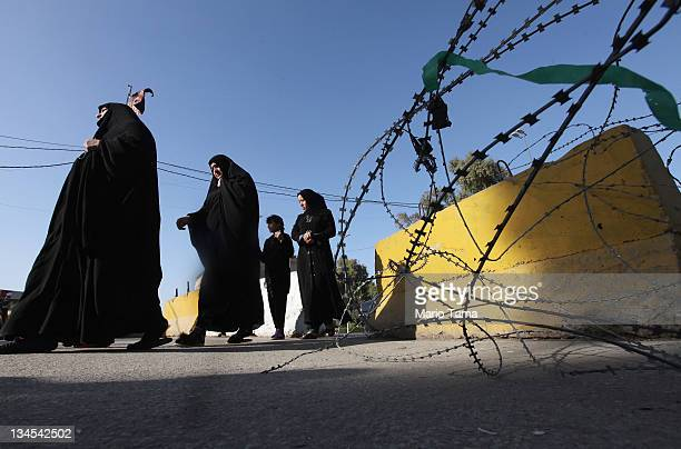 Women walk past barbed wire and barriers protecting a mosque on December 2 2011 in Baghdad Iraq Baghdad is enmeshed in heavy security as terrorism...