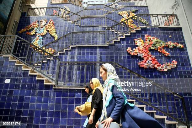 Women walk past decorated walls of stairs in Tehran Iran on May 08 2018