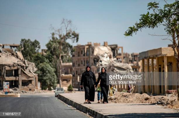 Women walk past destroyed buildings in the northern Syrian city of Raqa, the former Syrian capital of the Islamic State group, on August 21, 2019. -...