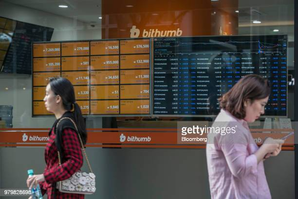 Women walk past monitors displaying the prices of cryptocurrencies at a Bithumb exchange office in Seoul South Korea on Wednesday June 20 2018...