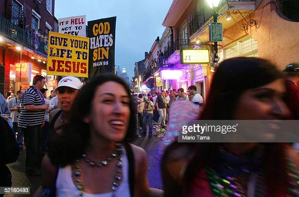 Women walk past people holding religious signs on Bourbon Street during Mardi Gras festivities February 8 2005 in New Orleans Louisiana Mardi Gras is...