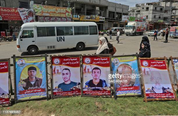 Women walk past posters of Palestinians prisoners held in Israeli jails, put up to mark Palestinian Prisoners' Day and calling for their release, in...