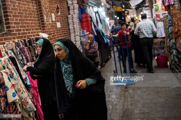 Women walk past stores selling household goods and fabrics inside the Grand Bazaar in Tehran Iran on Monday Aug 6 2018 Irans central bank acting on...