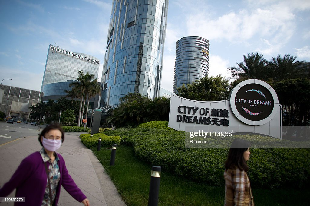 Women walk past the City of Dreams complex, operated by Melco Crown Entertainment Ltd., in Macau, China, on Wednesday, Feb. 6, 2013. Casino industry revenue in the gambling hub climbed 14 percent to a record 304 billion patacas ($38 billion) last year. Photographer: Lam Yik Fei/Bloomberg via Getty Images