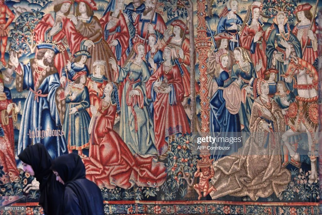 Women walk past the medieval 'Tapestry of Daniel and Nebuchadnezzar' displayed at the Louvre Abu Dhabi Museum during a media tour on November 6, 2017, prior to the official opening of the museum on Saadiyat island in the Emirati capital on November 8. More than a decade in the making, the Louvre Abu Dhabi opens its doors this week, bringing the famed name to the Arab world for the first time. The museum currently has some 300 pieces on loan, including an 1887 self-portrait by Vincent van Gogh and Leonardo da Vinci's 'La Belle Ferronniere'. /