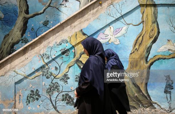 Women walk past the stairs with mural paintings on the walls in Tehran Iran on May 08 2018