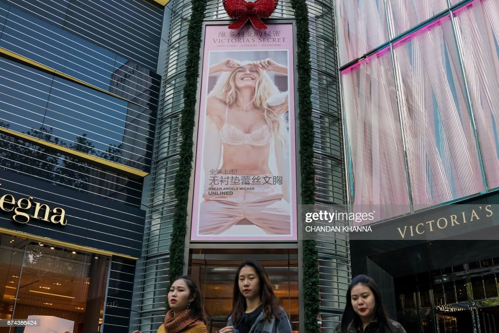 Women walk past the Victoria's Secret showroom in Shanghai on November 15, 2017. Victoria's Secret will be holding its annual fashion show in Shanghai in November. / AFP PHOTO / Chandan KHANNA