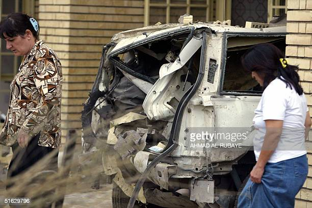 Women walk past the wreckage of vehicles following a car bomb outside the villa housing the Dubaibased AlArabiya satellite television station...