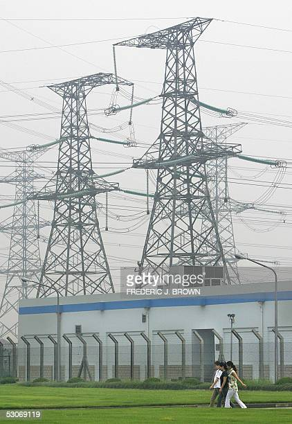 Women walk past towering pylons for power and electricity, 10 June 2005 oustside of Hangzhou, in China's southeast Zhejiang province. Energy-hungry...