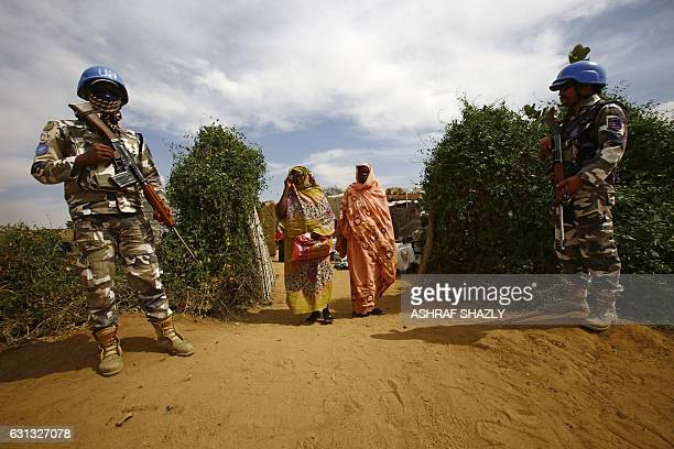 Women walk past UN peacekeepers standing guard at the Attash refugee camp in Nyala in South Darfur on January 9, 2017 following a visit by British...