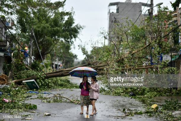 Women walk past uprooted trees in central Vietnam's Quang Ngai province on October 28 in the aftermath of Typhoon Molave.