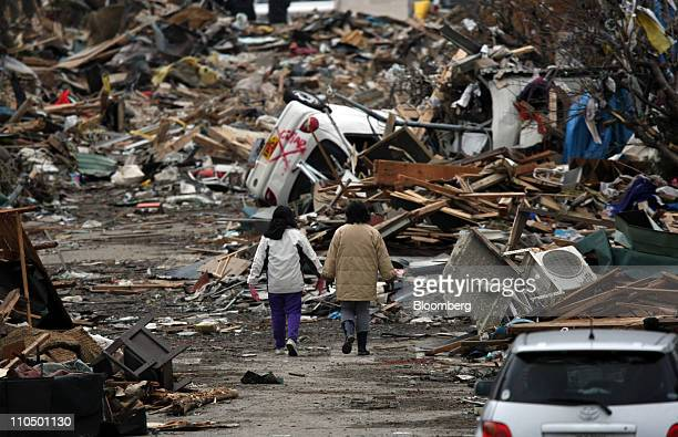 Women walk through a street covered with tsunami debris in Ofunato Iwate prefecture Japan on Monday March 21 2011The death toll following a magnitude...