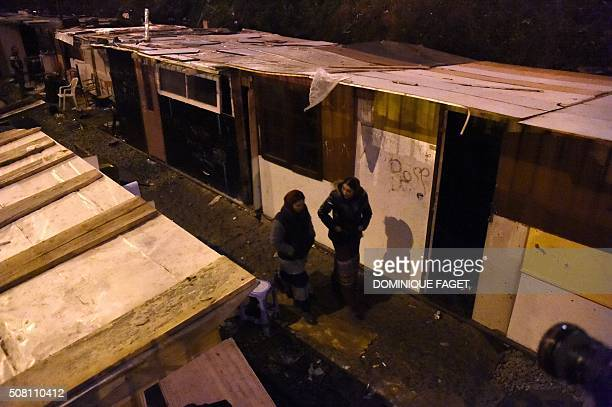 Women walk through makeshift shacks during the evacuation by Gendarmes of a Roma migrants' camp deemed insecure and unsanitary on former railway...