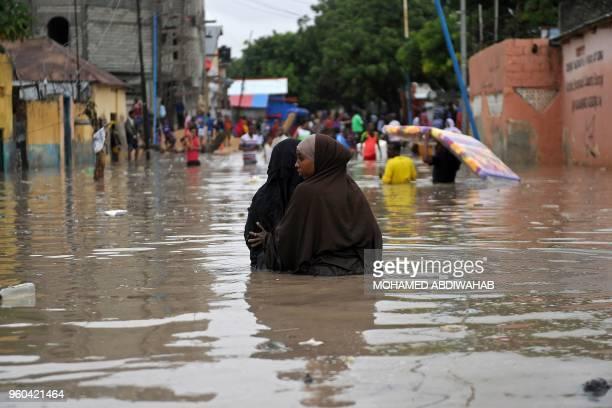Women walk through waistdeep flood water in a street of Mogadishu on May 20 2018 after homes were inundated in Somalia's capital following heavy...