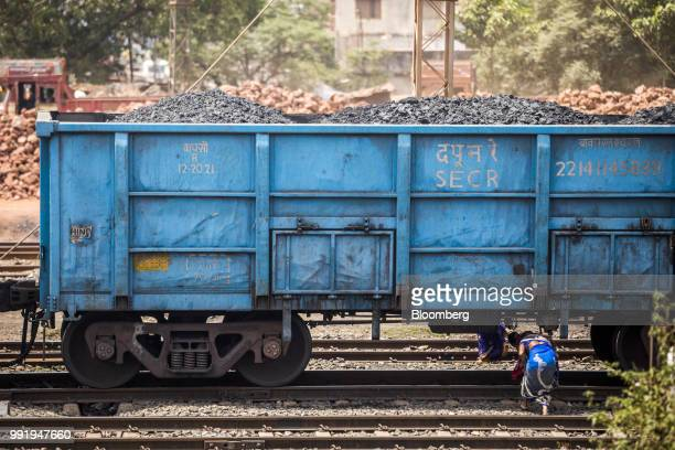 Women walk under a freight wagons laden with coal at the Tori Siding on the ToriShivpur rail line operated by Indian Railways and funded by Coal...