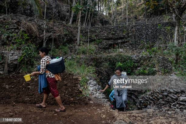Women walk while carrying jerrycans full of water from a cave at Klepu village Sawahan Kulon on August 28 2019 in Pacitan East Java province...