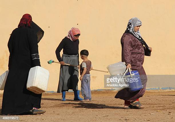 Women walk with water bins and buckets at the tent city close to Al Salama border gate in Azez district of Aleppo, Syria on September 29, 2014.