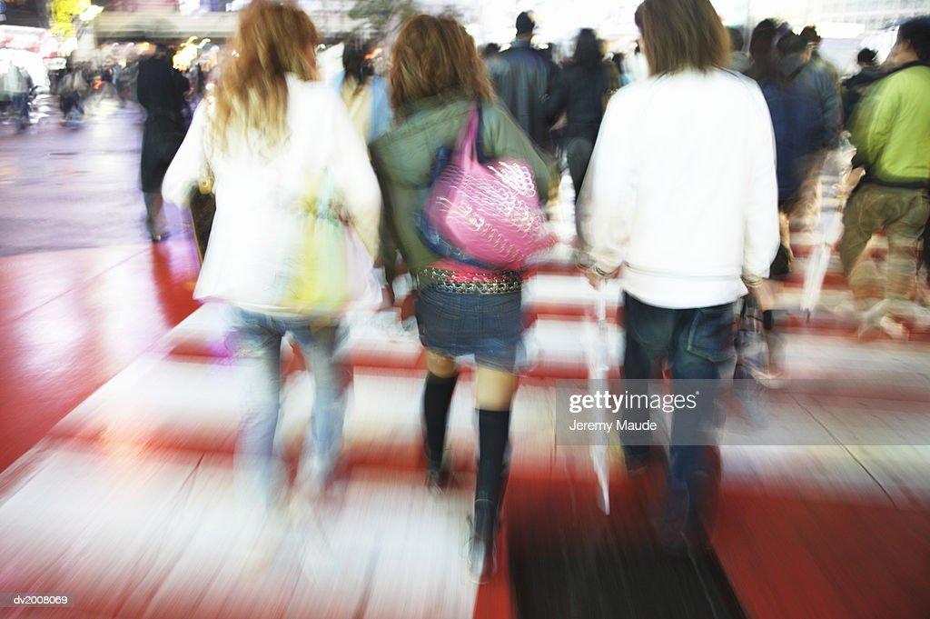 Women Walking Across a Busy Pedestrian Crossing in the City, Japan : Stock Photo