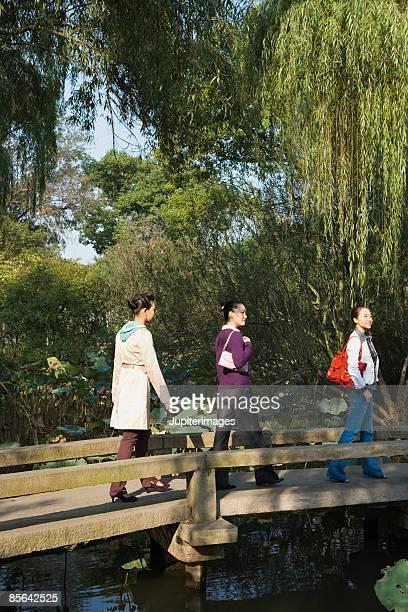 women walking across bridge - china oriental - fotografias e filmes do acervo