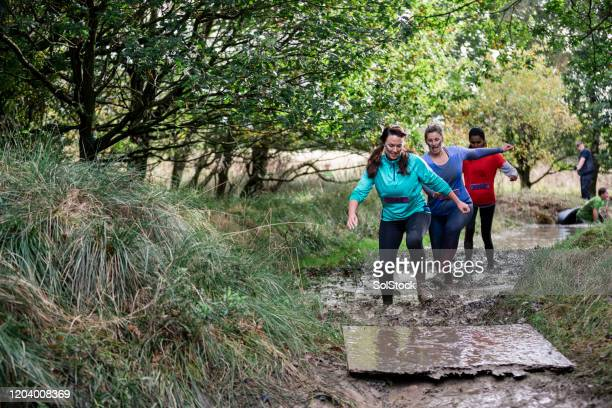 women walking along muddy path on cross country event - participant stock pictures, royalty-free photos & images