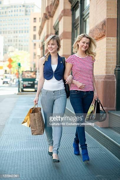 Women walking arm-in-arm on city street