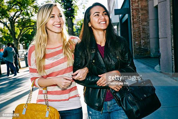 Women walking arm-in-arm on sidewalk