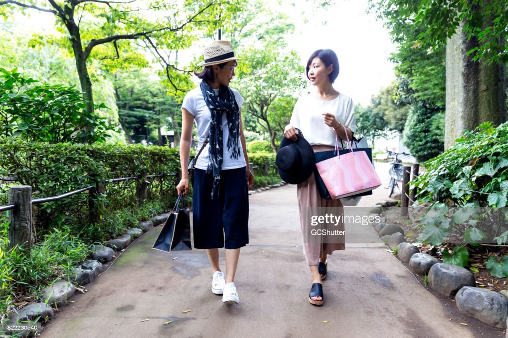 Women walking in a park with several bags in hand : Stock Photo