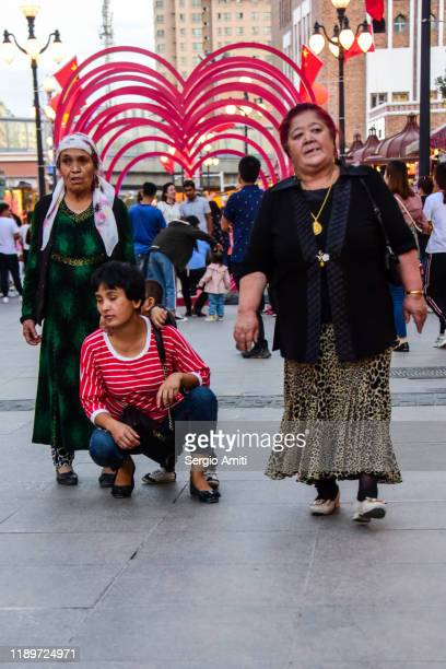 women walking in a pedestrian street in urumqi - sergio amiti stock pictures, royalty-free photos & images