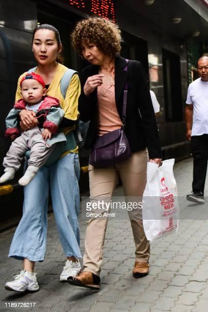 women walking in urumqi, xinjiang - sergio amiti stock pictures, royalty-free photos & images