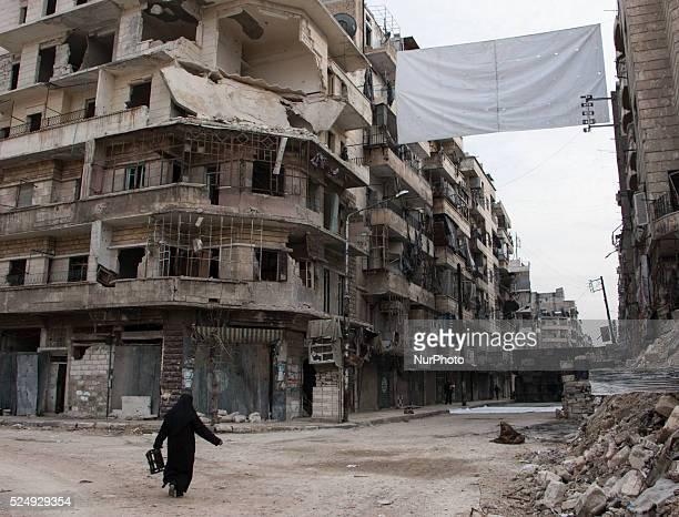 A women walking near one of curtains on Bustan Alqasr district in Aleppo city on 1st February 2016