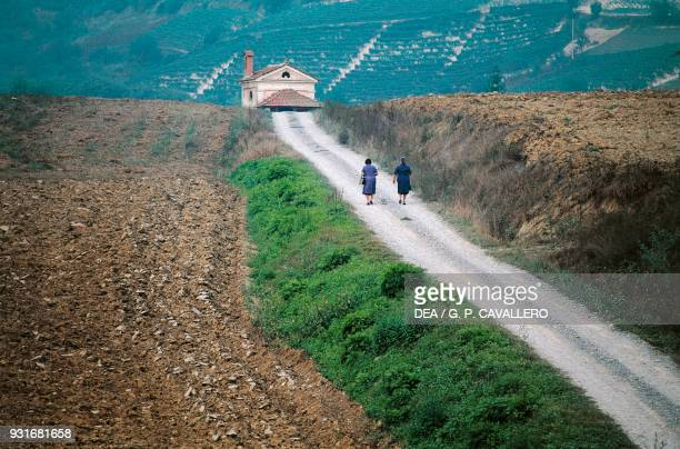 Women walking on a path leading to a church Bubbio Piedmont Italy