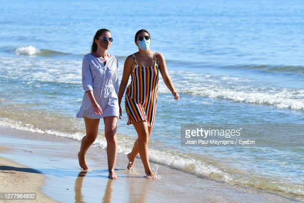 women walking on beach - valencia spain stock pictures, royalty-free photos & images