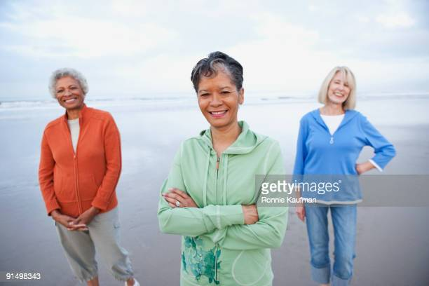 women walking on beach together - female friendship stock pictures, royalty-free photos & images