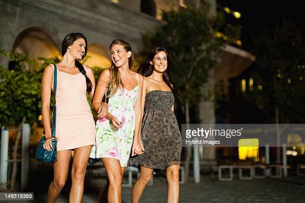 Women walking on city street at night