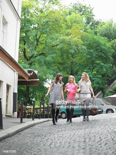 Women walking on cobbled street