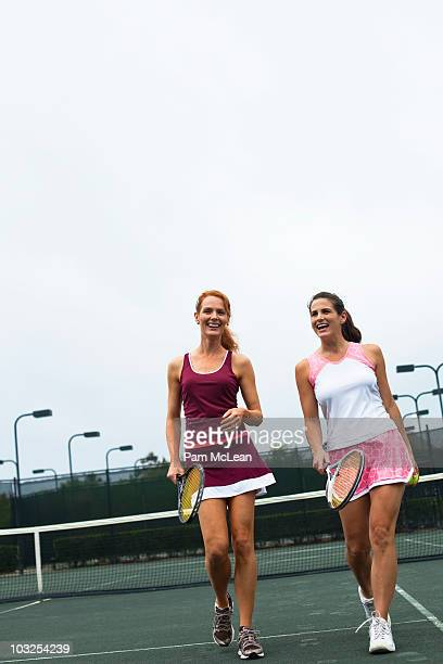 Women walking on tennis court