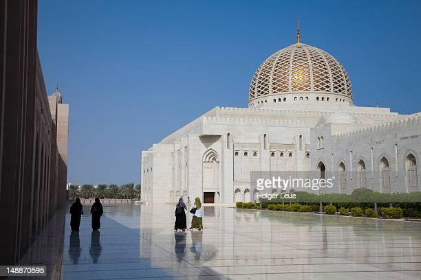 Women walking outside Sultan Qaboos Grand Mosque.
