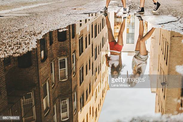 women walking through puddle on road, boston, ma, usa - women in wet t shirts stock pictures, royalty-free photos & images