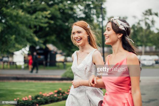 women walking to racecourse - fascinator stock pictures, royalty-free photos & images