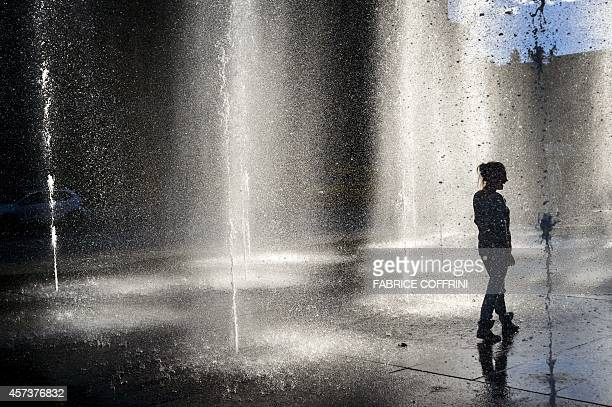 A women walks in a middle of the Federal square fountain on October 17 2014 in the Swiss capital Bern during the end of a warm autumn day AFP PHOTO /...