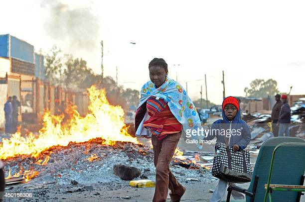 A women walks past a makeshift fire while taking her son to school in the early hours of the morning on June 5 2014 in Alexandra Township in...
